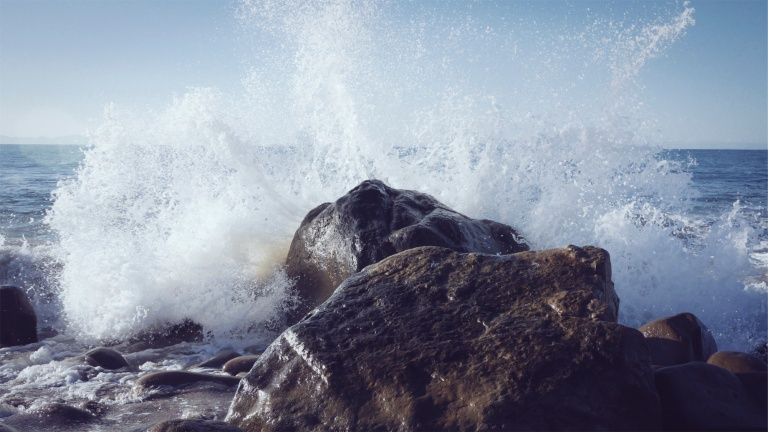 Ocean spray of water as it crashes on the rocks.
