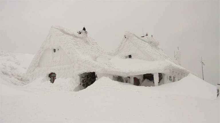 Winter in overdrive with this snow covered house.