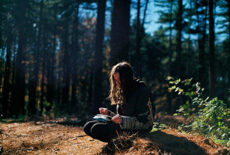 Young person in the woods writing in the quiet.